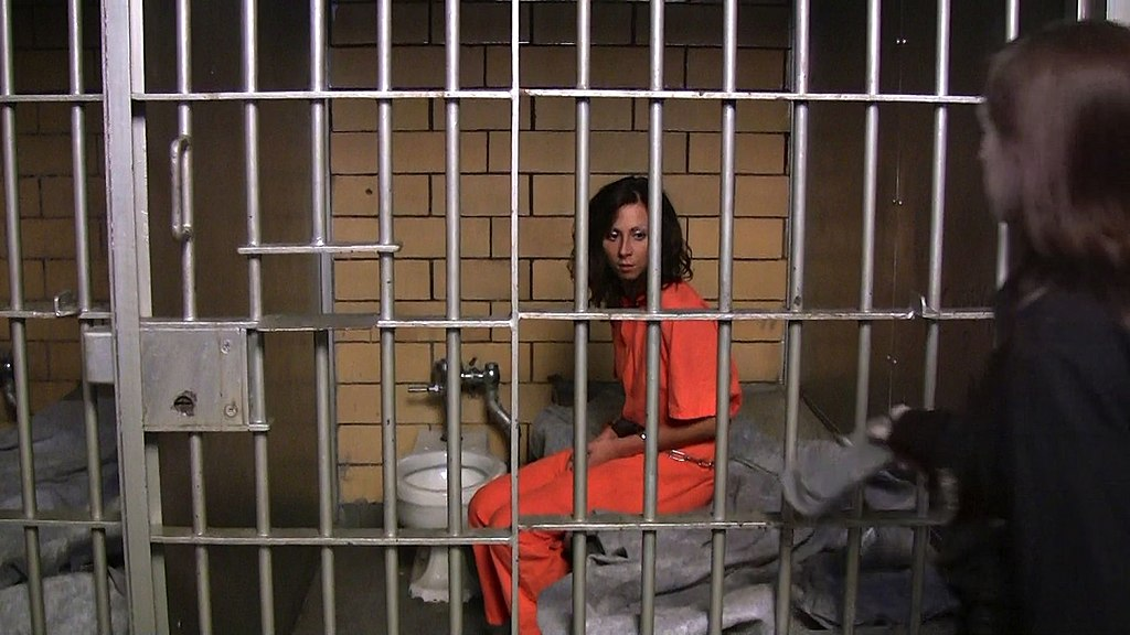 1024px-Female_prisoner_shackled_in_her_small_cell.jpg
