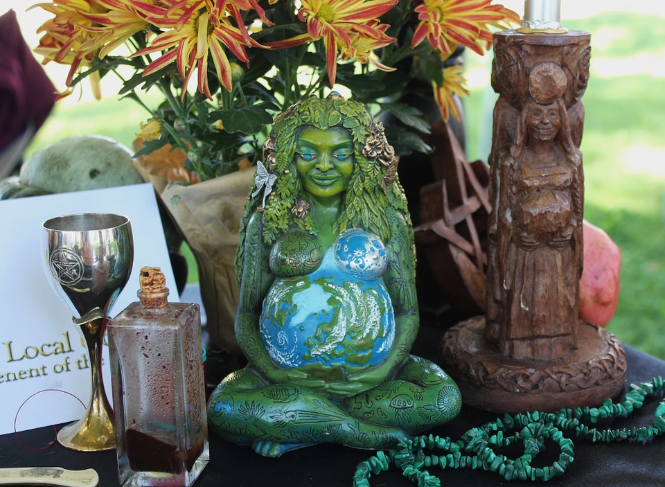 A Wiccan-style gathering of artifacts including a statue of a seated green goddess, her pregnant belly painted as the earth; mums; a chalice; a string of green beads; a stoppered rectangular prism bottle; and a candleholder appearing to be carved of wood, again of a pregnant woman with hands holding her belly.